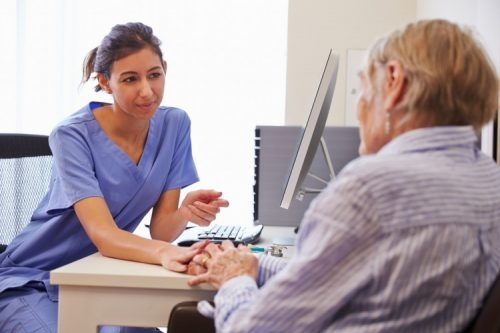 A nurse practitioner talks with a patient.