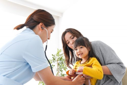 A nurse uses a stethoscope up to a child.