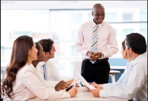 A group of professionals have a discussion around a conference table.
