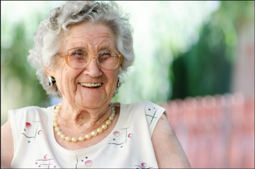An elderly woman smiles while seated outside.