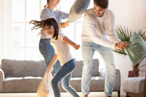 Two adults and a child have a pillow fight in a sunny living room.