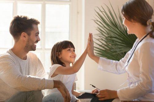 Un médecin félicite une petite fille sous le regard rieur de son père.