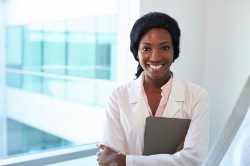 A smiling nurse holding a digital tablet.