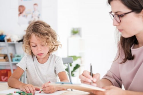 A therapist watches as a child draws pictures.