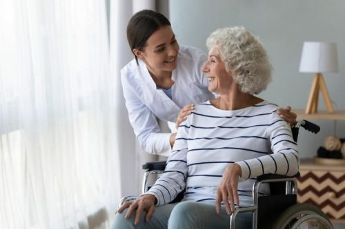 A senior patient sitting in a wheelchair by a window smiles at a nurse while receiving care.