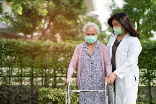 A nursing home administrator walks with a patient outside.