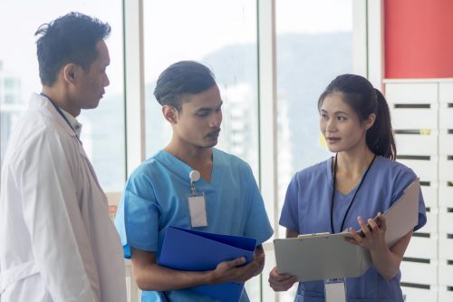 A nurse practitioner discusses a patient's chart with the medical team