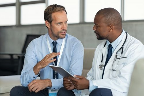 A health care executive meets with a doctor.