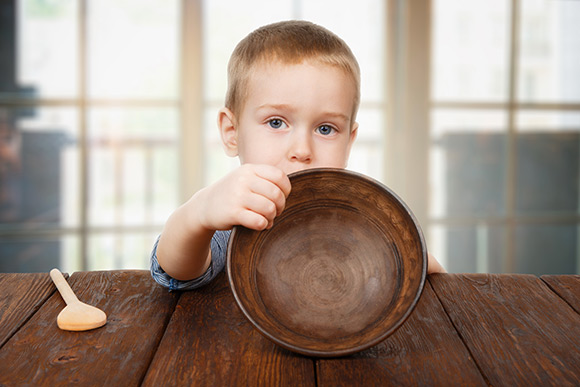 A boy sitting at a table holding an empty bowl