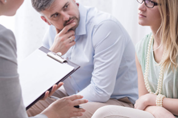 A man and a woman talking with a counselor in a counseling office