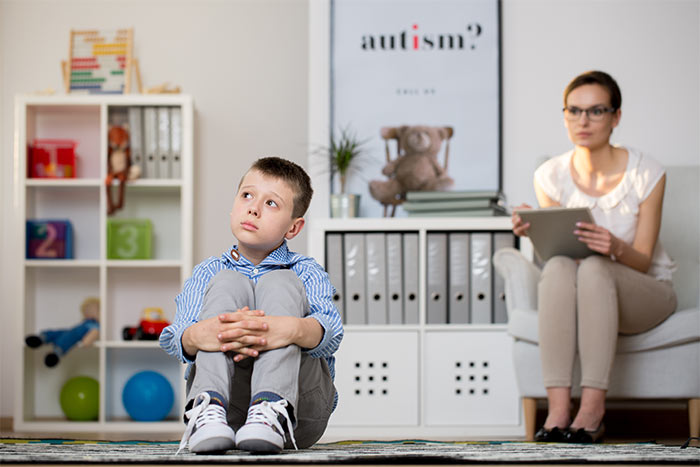 Child in room, woman watching with clipboard