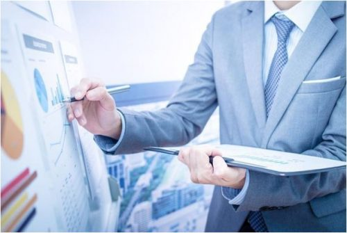 A tax professional works on a whiteboard