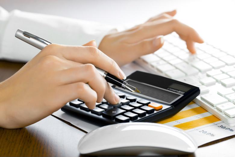 A finance professional uses a calculator and PC