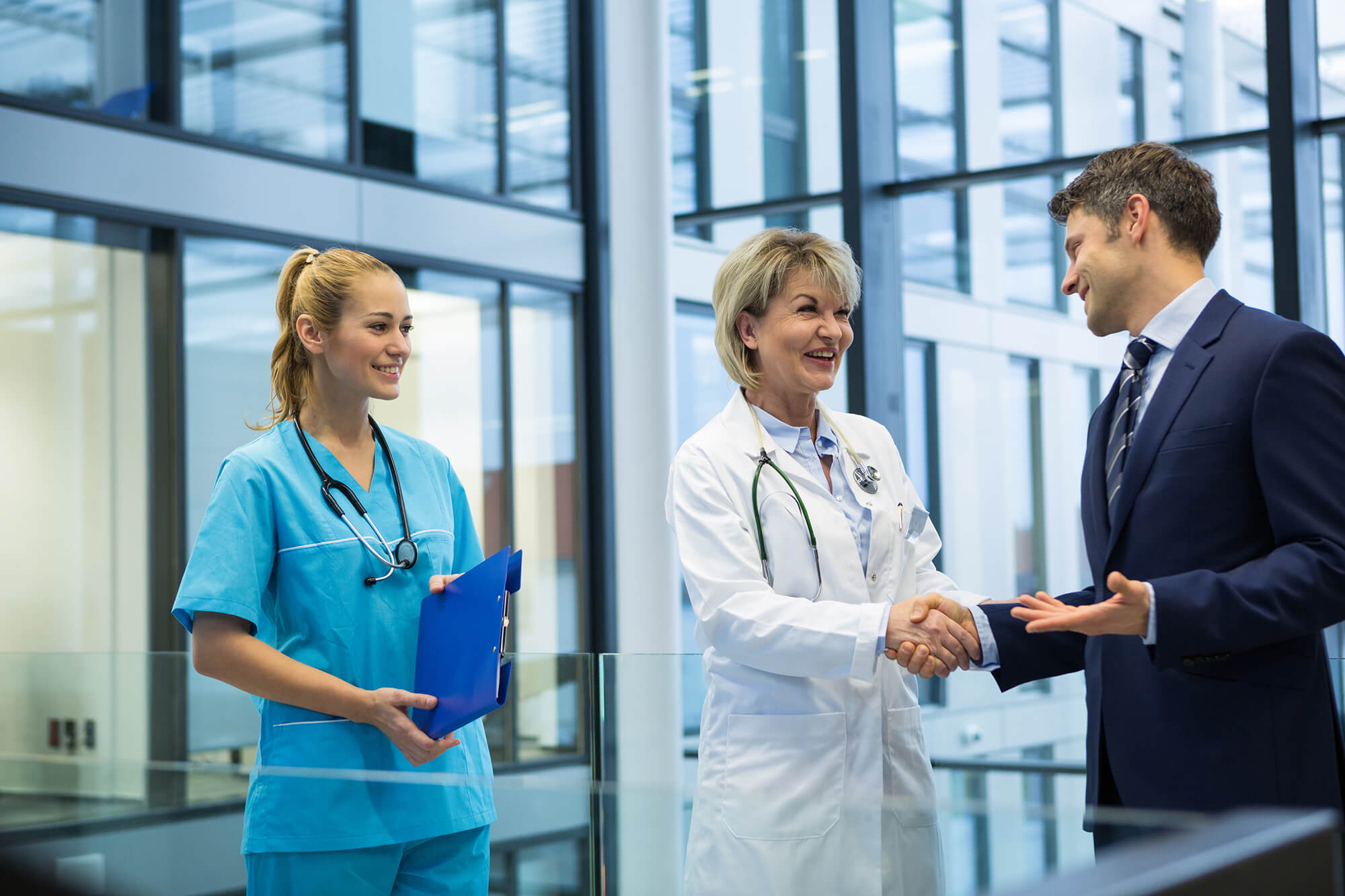 Healthcare Management Professional Greets a Doctor and a Nurse