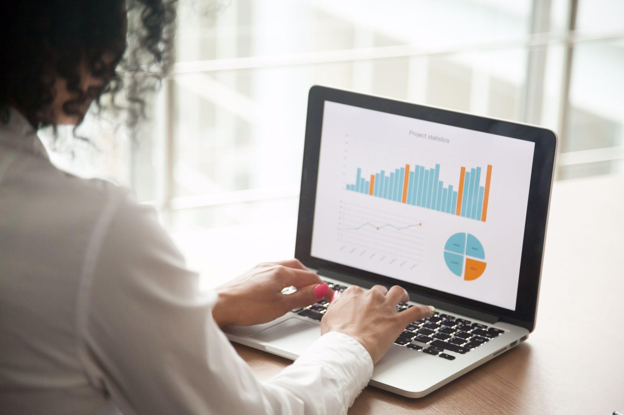 Woman at laptop analyzing charts
