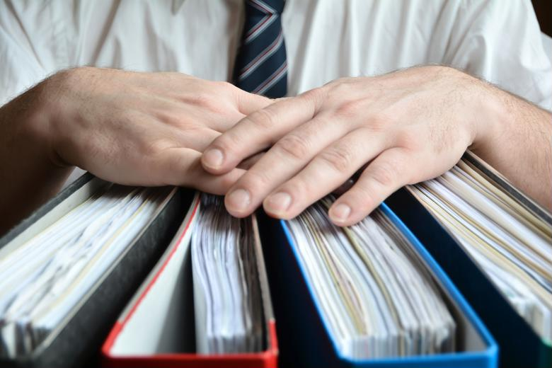 A tax accountant poses with binders of financial statements.