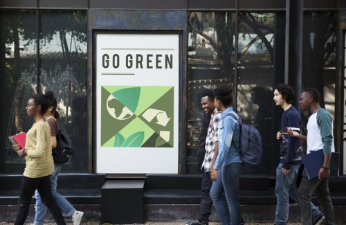 """Students walk by a poster that says """"Go Green""""."""