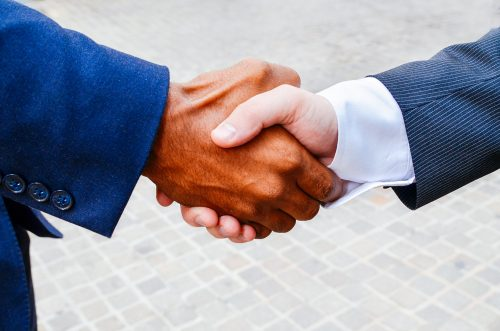 Two people in business suits shake hands.