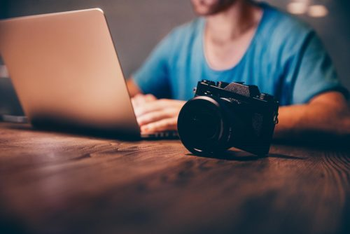 Man uploads images or video to his laptop from his camera.