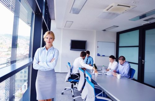 Female Healthcare MBA graduate standing by window in a corporate boardroom, with others in background