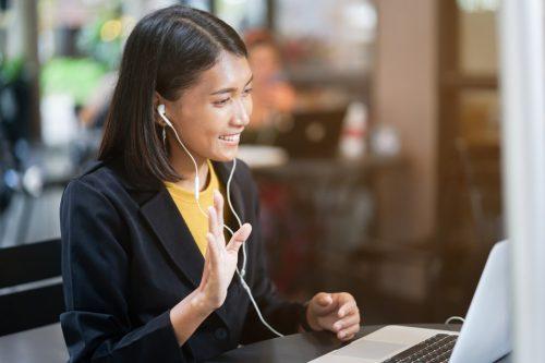 Remote worker greets members of her virtual team in online meeting.