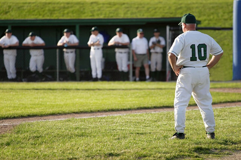 Baseball coach standing on the field in the summer