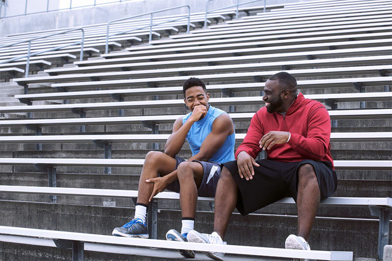 Male coach laughing with high school athlete