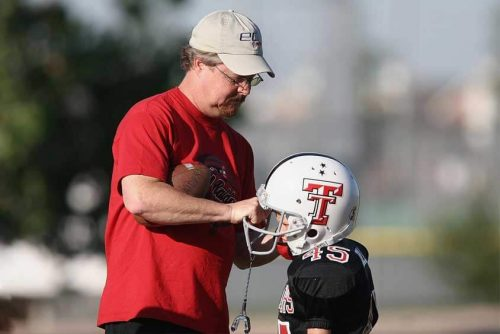 Youth football coach helping young player with helmet