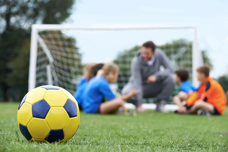 Soccer coach with players on field