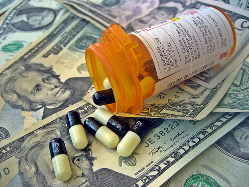 Open bottle of pills and money