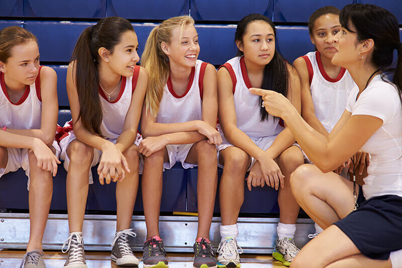 Female coach with basketball team