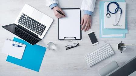 Overhead view of doctor writing on a clipboard