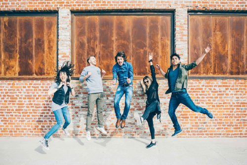 Young people jumping up in front of a building