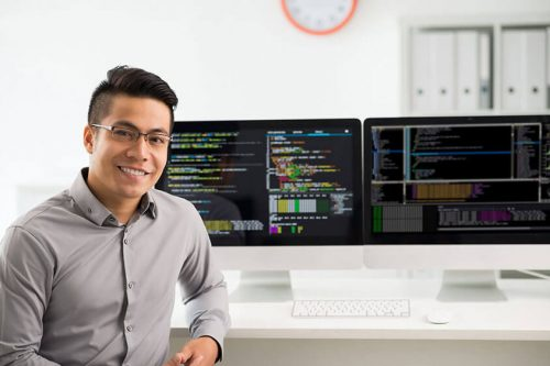 Male sitting in front of computer monitors