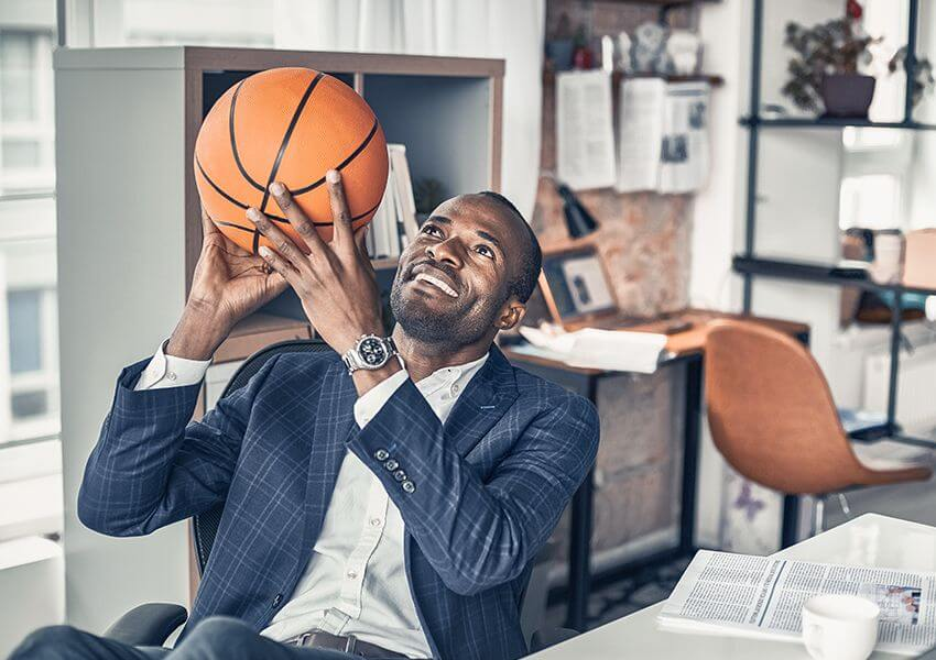 Man holding basketball while sitting at the desk