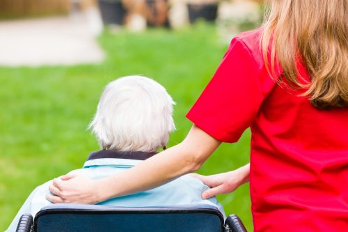Older woman in wheelchair with caregiver