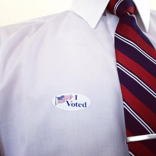 "Sticker attached to collared white shirt, reading ""I Voted."""