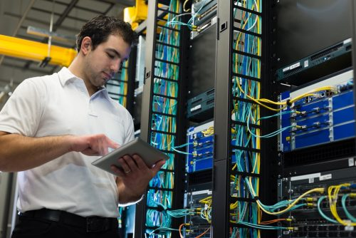Man with tablet surrounded by servers