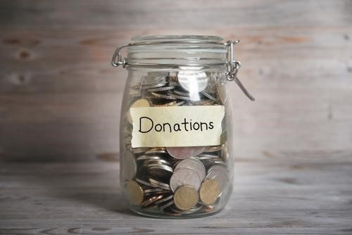"""Jar of coins with the word """"donations"""" on the label."""