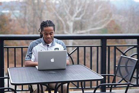 student studies outside with his laptop