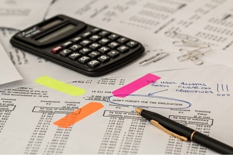 a calculator and a pen on top of financial documents