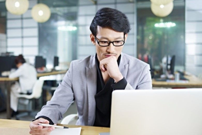 Man with glasses looking at laptop while thinking
