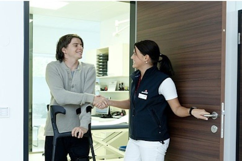 Man on crutches shaking hands with a nurse practitioner
