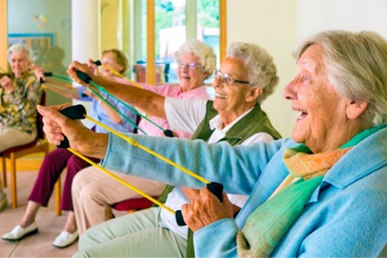 a group of elderly ladies doing exercises with elastic equipment