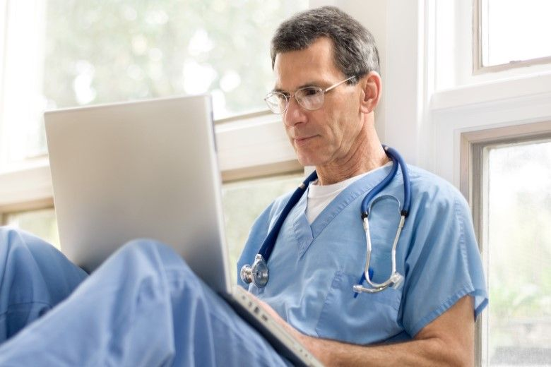 healthcare professional sitting on the ground while using his laptop