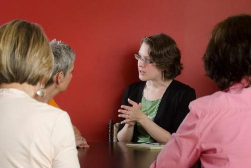 A media relations director consults with her team.
