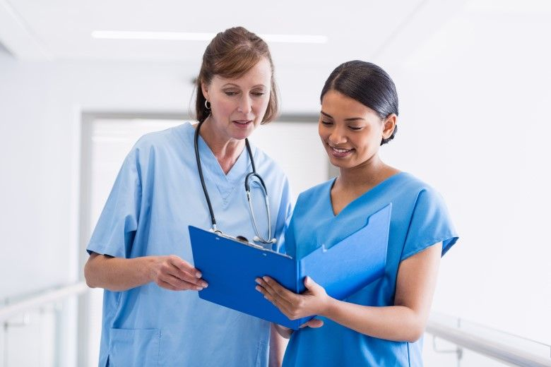 Nurse and doctor discuss over clipboard