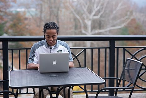 ohio university student studies at laptop