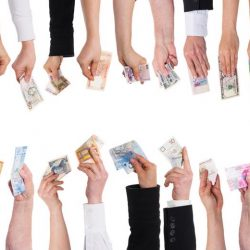 Stretched out hands holding money in different currencies