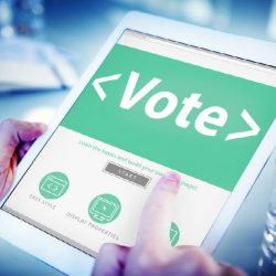 """Tablet held by man, with """"Vote"""" on the screen"""